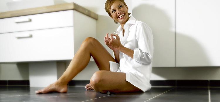 Femme assise sur plancher chauffant de salle de bains