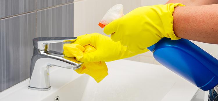 Nettoyage du calcaire avec gants jaunes et produit ménager