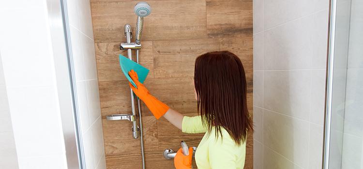 Une jeune femme nettoie le calcaire d'un espace douche
