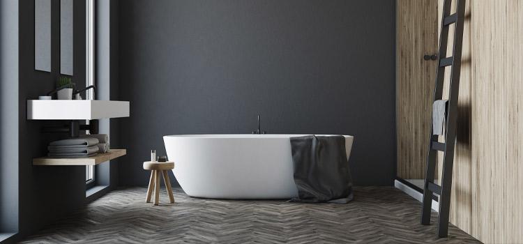 Salle de bains avec revêtement mural noir et baignoire hors sol