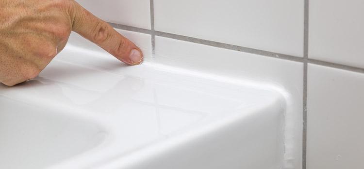 personne passant son doigt sur le joint d'une baignoire de salle de bains