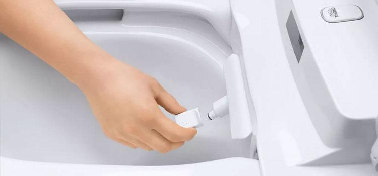 personne effectuant des réglages sur le WC lavant