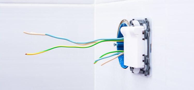 Câbles électriques dénudés qui sortent d'un mur carrelé
