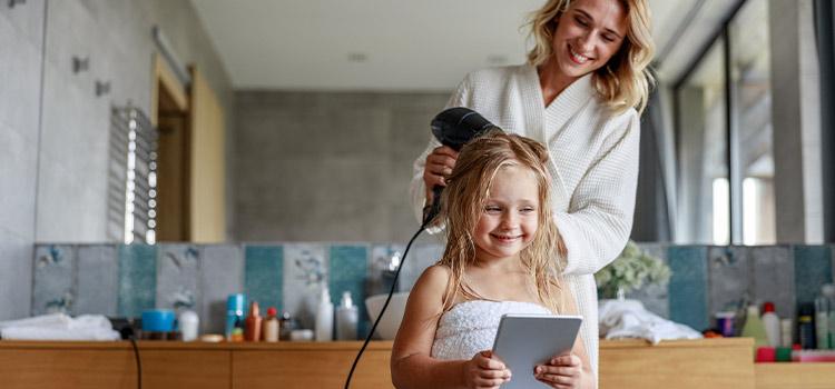 Maman qui sèche les cheveux de sa fille avec un sèche-cheveux
