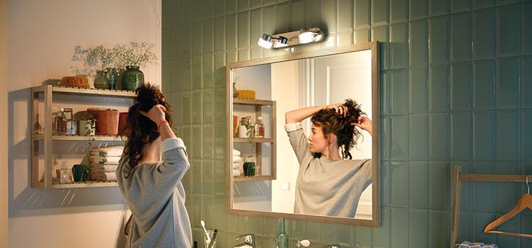 jeune femme qui se coiffe devant son miroir dans une salle de bains