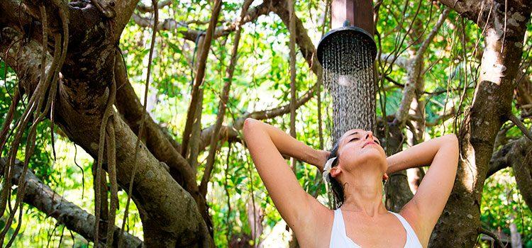 jeune femme profitant d'une douche à l'extérieur